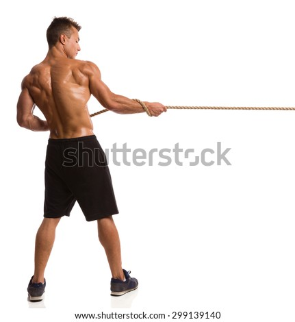 Strong Man Pulling A Rope. Muscular man in sport shorts and sneakers pulling a rope. Rear view. Full length studio shot isolated on white. - stock photo