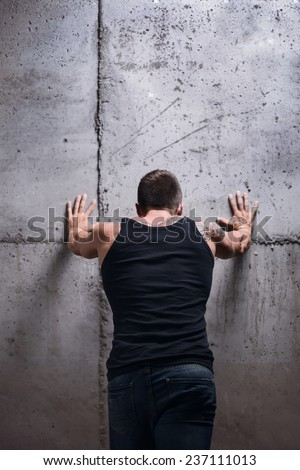 Strong man pushing the wall