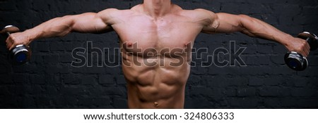 Strong man raises heavy dumbbells in his hands. He strained all the muscles of the body. Muscular man on dark background. He trains body and raises a lot of weight. Face is not visible, only body.