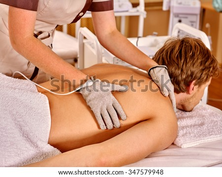 Strong man receiving back electric massage at beauty salon. Beautician wearing electricity gloves.  - stock photo
