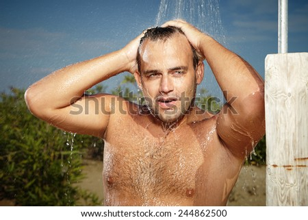 Strong man showering on beach - stock photo