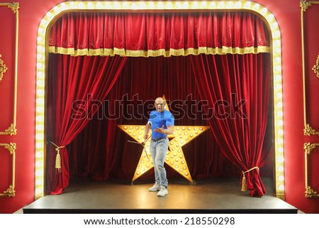 Strong man stands on stage holding microphone stand - stock photo