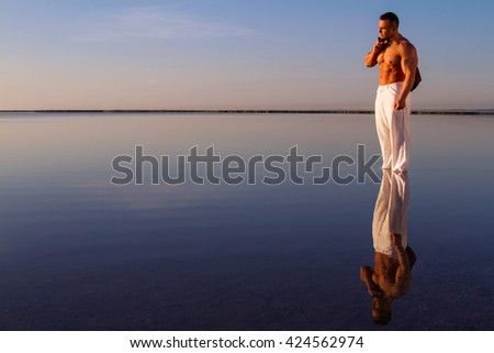 Strong man stay in the water and enjoy first rays of sun