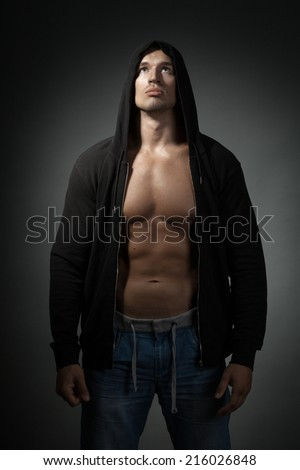 strong man wearing black hoodie isolated on dark background