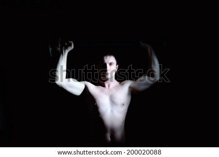 Strong man with a barbell look at cam - stock photo
