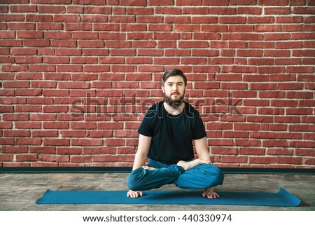 Strong man with a beard wearing black T-shirt and blue trousers doing yoga position padmasana asana on hands on blue matt at wall background, copy space, portrait. - stock photo
