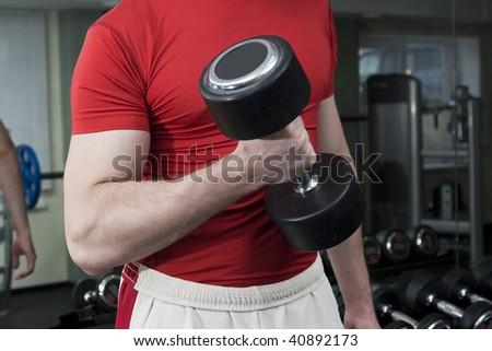 Strong man with dumbbells, focus on hand and dumbbell - stock photo