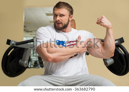 Strong man with huge muscles. Sportsman showing his muscles. - stock photo
