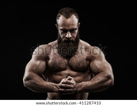 Strong man with perfect abs, shoulders, biceps, triceps and chest. Bodybuilder topless over black background. - stock photo