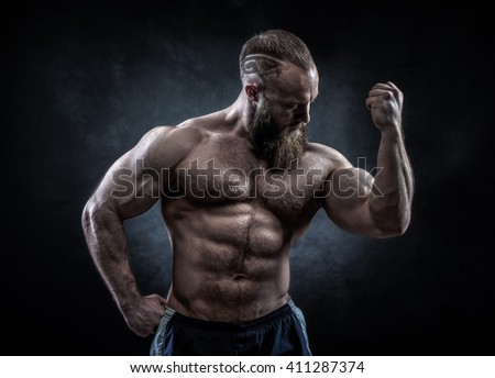 Strong man with perfect abs, shoulders, biceps, triceps and chest. Bodybuilder topless over grunge background. - stock photo