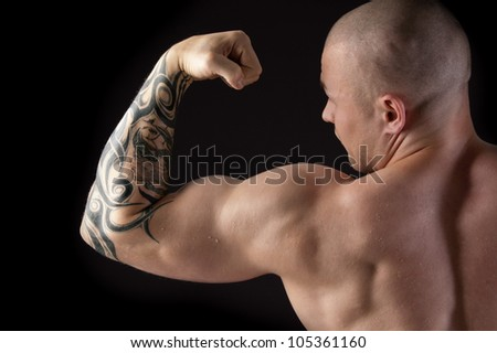 Strong man with relief body and a tattoo on his arm - stock photo