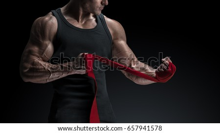 Strong man wrap hands on black background Man is wrapping hands with red boxing wraps isolated on black background Strong hands and fist, ready for training and active exercise