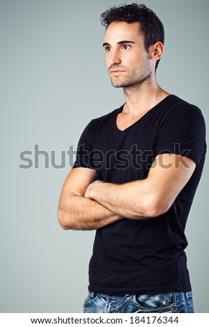 Strong masculine man standing firm with his arms crossed. - stock photo