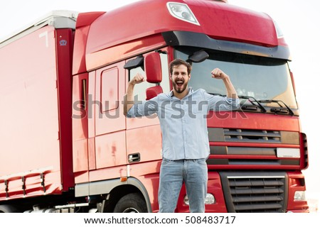 strong masculine truck driver standing outside and showing his muscle with his vehicle behind