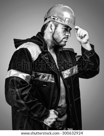 Strong men worker in the helmet and workwear - stock photo