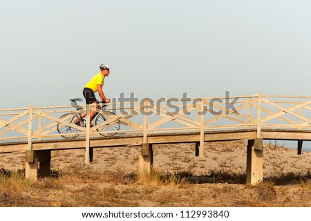 Strong middle aged man riding a bicycle over a wooden bridge at the seaside with the fresh air