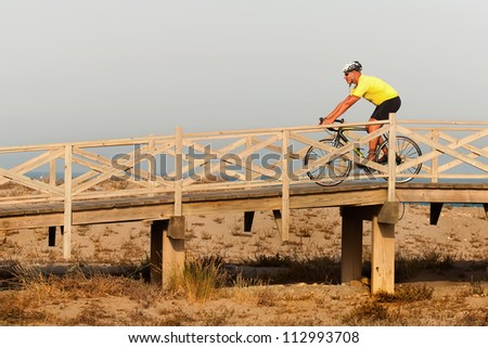 Strong middleaged man riding a bicycle over a wooden bridge at the seaside with the fresh air