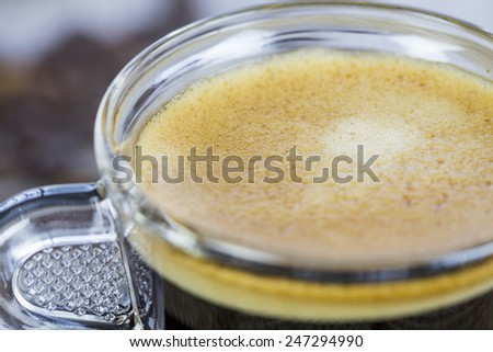 Strong mug of freshly brewed espresso coffee with coffee beans with a dainty pile of crunchy cookies tied together on a hessian cloth - stock photo