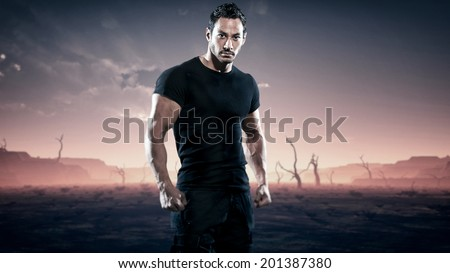 Strong muscled hero fitness man standing in desolate landscape with dead trees. Sunset. - stock photo