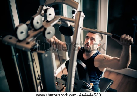 Strong muscular bodybuilder doing exercise on rowing machine in the gym. Part of fitness body. Sports and fitness. Fitness man in the gym.Strong man at the gym lifting weights.Low key - stock photo