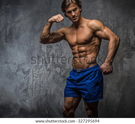 Strong muscular bodybuilder showing his body. Isolated on grey background.