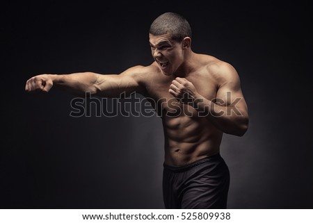 Strong muscular boxer. Isolated on black background