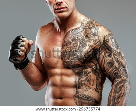 Strong muscular fighter with tattoo poses - stock photo