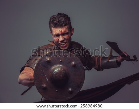 Strong muscular gladiator attacks holding sword and shield