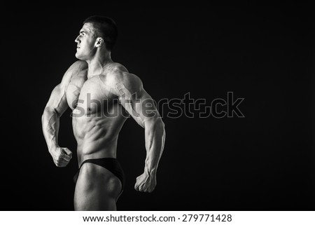 Strong, muscular guy on a black background. Man posing, man straining muscles. Muscles of the arms, torso, abdominal muscles. - stock photo