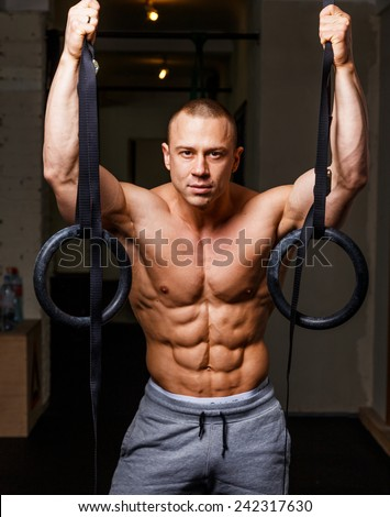 Strong muscular man bodybuilder poses and shows his abs - stock photo