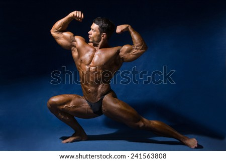 Strong muscular man bodybuilder shows his muscles. Mandatory athlete fitness pose on a blue background - stock photo