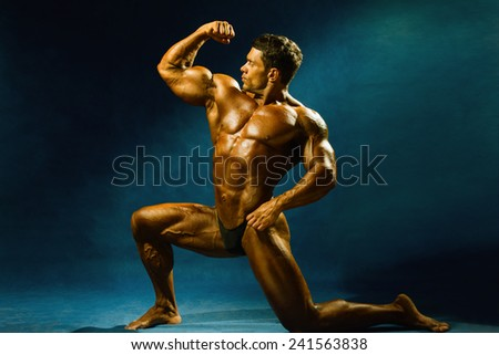 Strong muscular man bodybuilder shows his muscles. Sportsman fitness - stock photo