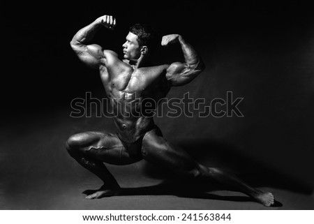 Strong muscular man bodybuilder shows his muscles. Sportsman fitness monochrome horizontal image - stock photo