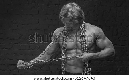 Strong muscular man breaks the chains on his body. Black and white image.