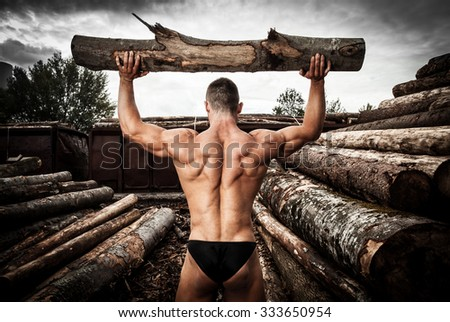 Strong muscular man holding heavy wood trunks - stock photo