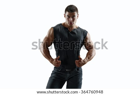 Strong muscular man in a T-shirt and jeans, showing raised up thumbs. Isolated. - stock photo