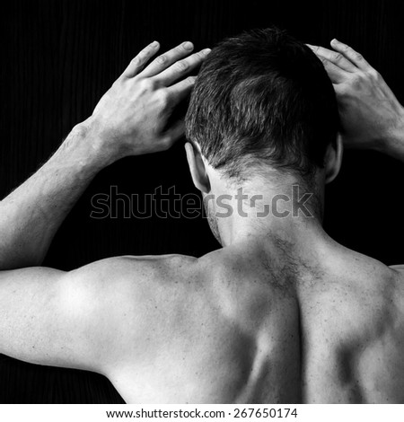 Strong muscular young Caucasian man stands near black wall, black and white photo - stock photo
