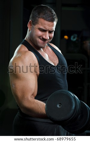 Strong muscullar man training body in gym. - stock photo
