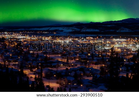 Strong northern lights (Aurora borealis) substorm on night sky over downtown Whitehorse, capital of the Yukon Territory, Canada, in winter. - stock photo
