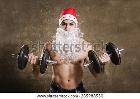 Strong Santa Claus training biceps on dirty wall background