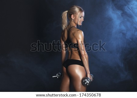strong sexy woman is training with dumbbells  - stock photo