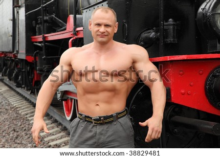 strong shirtless man against locomotive