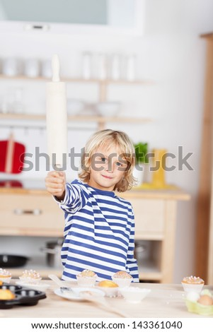 Strong small young blonde caucasian girl, playing in the kitchen holding a rolling-pin high near muffins - stock photo