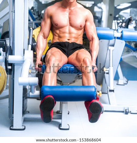 strong sportsman doing leg exercises at the gym - stock photo