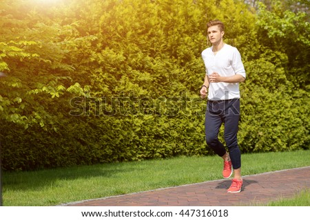 Strong sportsman jogging in the nature - stock photo