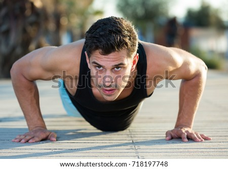 Strong sporty man doing push-ups during daily workout outdoors