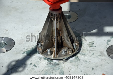 Strong stainless steel bolts hold this heavy metal base plate in place, with precision. - stock photo