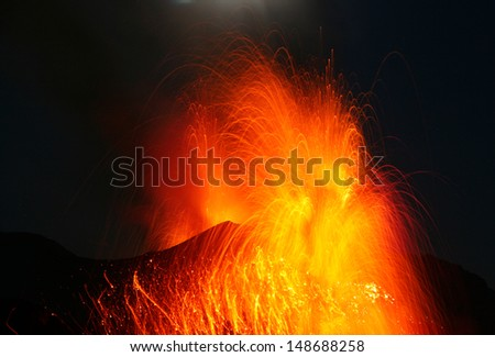 Strong strombolian type volcanic eruption at night with glowing lava bombs flying around - stock photo