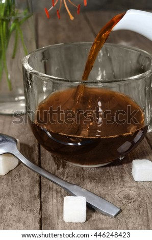 Strong tea is poured into a glass Cup, close-up on the old boards