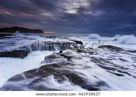 strong tide wave undermining sandstone rocks near Collaroy northern beaches of Sydney at sunrise. Dramatic weather hides rising sun.